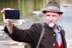Bayersk man i hans 50-tal som står vid floden och tar en selfie Fotografering för Bildbyråer