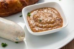Bayersk söt senap med den tyska den Munich Weißwurst korven och kringlan arkivfoton