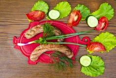 Bayerska korvar på en skärbräda med grönsaker arkivbild
