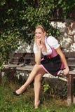 Bayerskt blont flickasammanträde kopplade av på en bänk i en dirndl royaltyfri fotografi