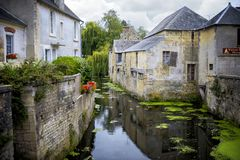Bayeux, France - Scene of Bayeux with a waterway named the Aure. Bayeux. The city is also known for its famous Bayeux Tapestry, which can be visited in its Stock Photos