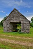 Baler in an old corn crib. An old weathered wood corn crib    provides shelter to a vintage hay baler Stock Image