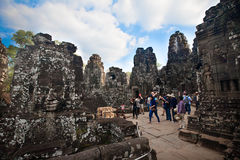 参观Bayon寺庙,一部分的清早游人的吴哥城废墟古庙柬埔寨 免版税库存照片