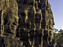 Bayon faces 1. Three giant ancient khmer stone face sculptures in yellow light at sunset royalty free stock image