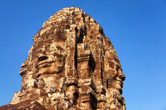 Bayon Temple in Angkor Wat, Cambodia. Stone carved faces of Bayon Temple in Angkor Thom, Angkor district, Siem Reap, Cambodia. Horizontal shot, sky on background Royalty Free Stock Images