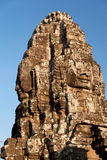 Bayon Temple in Angkor Wat, Cambodia. Stone carved faces of Bayon Temple in Angkor Thom, Angkor district, Siem Reap, Cambodia. Vertical shot, sky on background Stock Photography