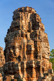 Bayon Temple in Angkor Wat, Cambodia. Stone carved faces of Bayon Temple in Angkor Thom, Angkor district, Siem Reap, Cambodia. Vertical shot, sky on background Stock Photos