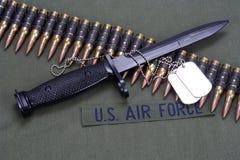 Bayonet, dog tags and ammunition belt on US AIR FORCE uniform background. Bayonet, dog tags and ammunition belt on US AIR FORCE uniform stock photography