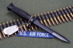 Bayonet, dog tags and ammunition belt on US AIR FORCE uniform. Background royalty free stock image