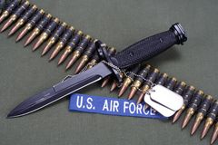 Bayonet, dog tags and ammunition belt on US AIR FORCE uniform. Background royalty free stock photo