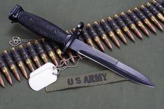 Bayonet, dog tags and ammunition belt on US ARMY uniform background. Bayonet, dog tags and ammunition belt on US ARMY uniform stock images