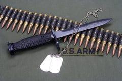 Bayonet, dog tags and ammunition belt on US ARMY uniform. Background royalty free stock image