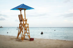 Baywatch chair in a beautiful beach empty at summer sunset. Stock Photo