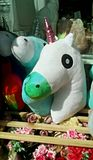Toy ornament. White plush unicorn toys on wooden shelf in street near other ornament stuff for sale royalty free stock image