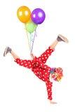 Błazenu mienia balony i pozycja na jeden ręce Zdjęcia Stock