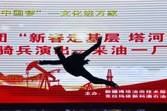 Bazhou, Xinjiang, China: As empresas misturadas da posse realizam a atividade 'de tomar a cultura das bases em dez mil casas foto de stock