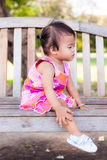 Bébé asiatique s'asseyant sur le banc Photographie stock libre de droits