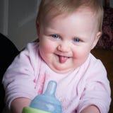 Bébé aux yeux bleus suçant la bouteille Photo libre de droits