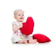 Bébé avec l'oreiller dans la forme de coeur Photographie stock libre de droits