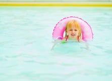 Bébé avec la natation d'anneau de bain dans la piscine Photos stock