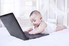 Bébé curieux jouant avec l'ordinateur portable Images stock