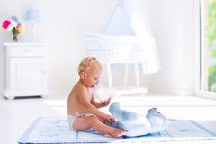 Bébé garçon avec la bouteille à lait dans la crèche ensoleillée Images stock
