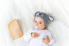 Bébé garçon dans le chapeau de souris se trouvant sur la couverture avec du fromage Photos libres de droits