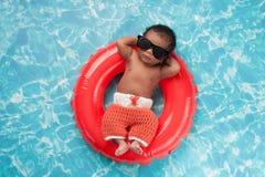 Bébé garçon nouveau-né flottant sur un anneau de bain Images libres de droits