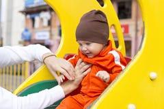 Bébé garçon sur la glissière des enfants Photo libre de droits
