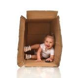 Bébé heureux de petit enfant se cachant dans une boîte en carton ayant le fu Images libres de droits