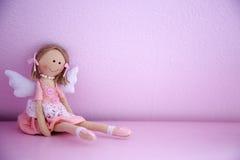 Bébé - poupée sur le mur rose Image stock