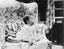 Bébé s'asseyant sur le fauteuil (toutes les personnes représentées ne sont pas plus long vivantes et aucun domaine n'existe Garan Images stock
