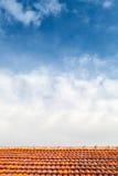 Bbackground con el tejado de teja roja y el cielo nublado azul Foto de archivo libre de regalías