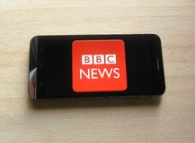 BBC News app. On smartphone kept on wooden table stock photo