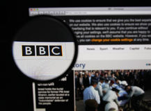 BBC. Photo of BBC homepage on a monitor screen through a magnifying glass Stock Photo