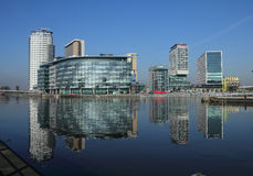 Salford Quays. British Broadcasting Corporation (BBC) studios, Salford University and surrounding apartments reflected in quays dock on a clear winters day Stock Image