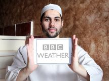 BBC Weather logo. Logo of BBC Weather on samsung tablet holded by arab muslim man. BBC Weather is the BBC`s department in charge of preparing and broadcasting Stock Photos
