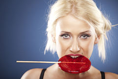 Bbeautiful blonde model with a red lollipop Royalty Free Stock Photography