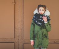 Bbeautiful unusual girl in a green jacket next to the brown door Stock Photo