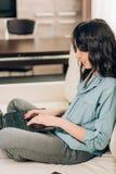 Bbeautifulvrouw die laptop computer thuis op bank met behulp van royalty-vrije stock fotografie