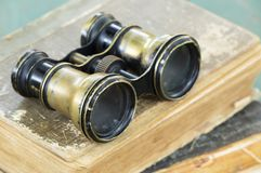 Binoculars on books, searching wisdom, knowledge. Vintage binoculars on old books, searching wisdom and knowledge concept royalty free stock photography