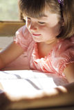 A Bíblia Sagrada bonita da leitura da menina Imagens de Stock