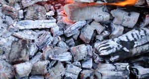 BBQ与发光和发火焰热的煤炭的格栅坑 库存照片
