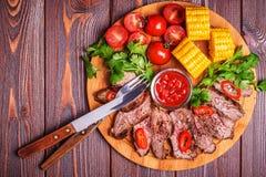 BBQ与菜和草本的羊羔牛排在黑暗的木背景 免版税库存照片