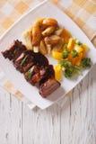 BBQ与菜的猪排在板材 垂直的顶视图 库存照片