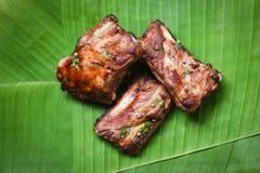 Bbq排骨烤用在香蕉叶子供食的草本香料-烤烤肉猪排切了 免版税库存照片