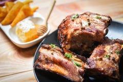 Bbq排骨烤用蜂蜜甜调味汁和草本香料在桌-被切的烤烤肉猪排上服务 库存图片