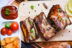 Bbq排骨烤用西红柿酱和草本香料在桌-烤烤肉猪肉上的木切板服务 库存图片