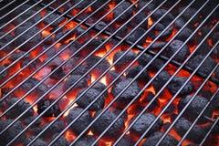 BBQ格栅和发光的热的木炭冰砖在背景中 免版税库存图片