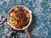 BBQ κοτόπουλο και ψημένα στη σχάρα λαχανικά σε ένα skillet χυτοσιδήρου σε ένα σκοτεινό υπόβαθρο, τοπ άποψη Στοκ Εικόνα
